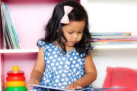 children education: Child read, cute little girl reading a book on bookshelf background