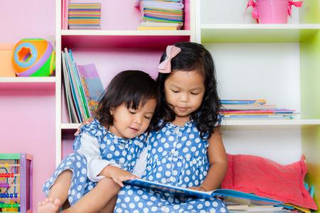 niños en la escuela: De lectura para niños, dos niñas lindas de leer el libro juntos en el fondo estantería