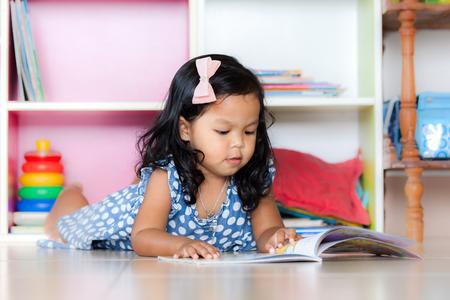 niño preescolar: Niño leer, linda niña leyendo un libro y acostado en el piso en el fondo estantería