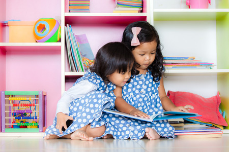 Child read, two cute little girls reading book together on bookshelf background