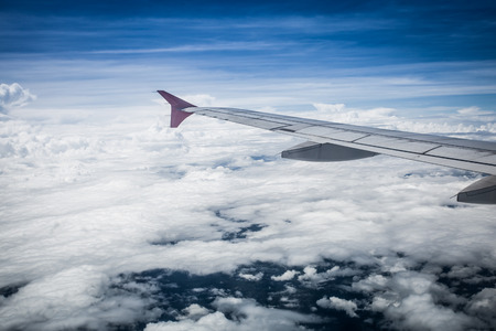 window view: View of cloud sky and wing of airplane from window