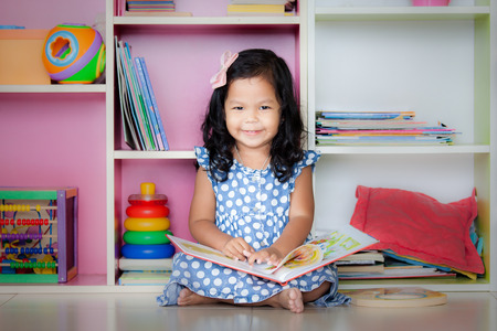 child sitting: Child read, cute little girl is smiling and reading a book and sitting on floor Stock Photo