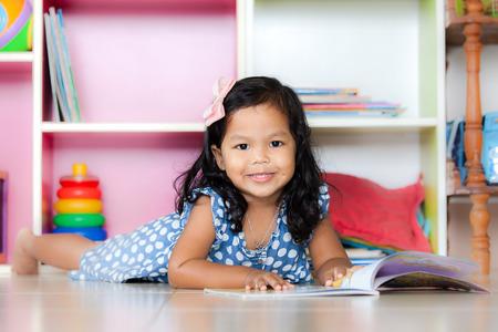 jolie fille: Enfant lire, mignonne petite fille lisant un livre et couch� sur le plancher sur �tag�re fond