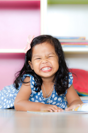 curly hair child: happy cute little girl smiling and lying on floor Stock Photo