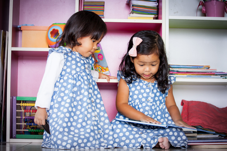 female student: Child read, two cute little girls reading book together on bookshelf background