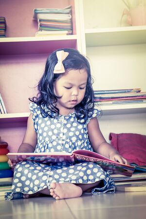 child sitting: Child read, cute little girl reading a book and sitting on floor,vintage filter