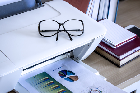 typer: eyeglasses on printer with books on wooden table