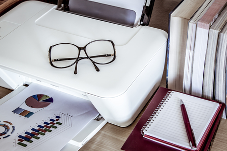 typer: eyeglasses on printer with books on wooden table,vintage filter