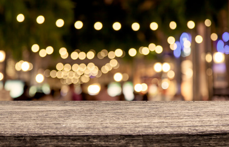 gold road: wooden table with abstract bokeh in night shopping mall  background