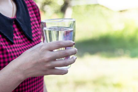 tomando refresco: Mano de la mujer que sostiene un vaso de agua fresca en el parque, filtro de color de la vendimia
