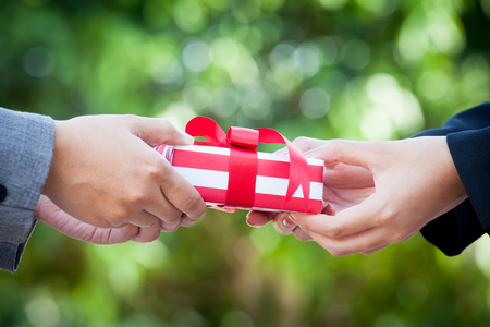 Business woman hand with christmas gift box on green bokeh background 写真素材