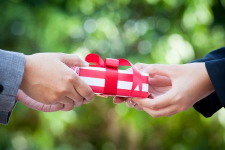 dar un regalo: Mujer de negocios de la mano con la caja de regalo de Navidad sobre fondo verde bokeh