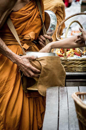 People give alms food and item offering to Buddhist monk at temple in  morning time,dark tone Stock Photo