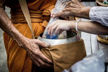 limosna: Las personas dan comida limosnas y el tema ofreciendo a monje budista en el templo en tiempo de la ma�ana, el tono oscuro Foto de archivo
