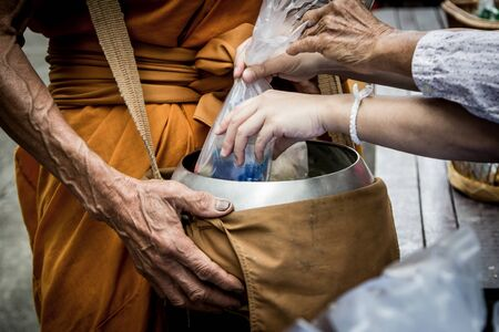 thai buddha: People give alms food and item offering to Buddhist monk at temple in  morning time,dark tone Stock Photo