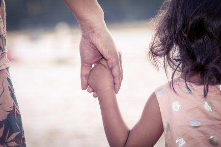 Kind niedliche kleine Mädchen und Mutter Hand zusammen mit der Liebe in Vintage Farbfilterhalte Standard-Bild - 48016076