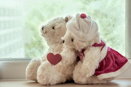osos navideños: Pareja osos de peluche en el abrazo de amor que se sienta delante de una ventana de día de lluvia, filtro de la vendimia Foto de archivo