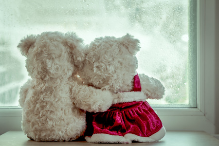 Couple teddy bears in love's embrace sitting in front of a rainy day window,vintage filter Archivio Fotografico