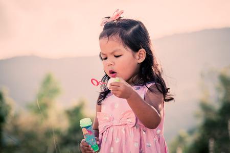 bubbles: Child cute little girl blowing a soap bubbles in the park,vintage filter