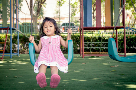 Child asian little girl having fun to play swing in children playground