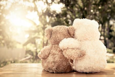 Pareja de osos de peluche en el abrazo de amor que se sienta en la mesa de madera en el jardín con la luz del sol, filtro de color de la vendimia