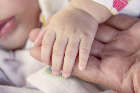 mother holding baby: newborn baby hand on mother hand, holding hand with love