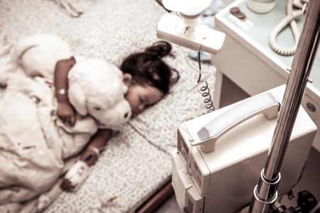 asian hospital: Sick little girl sleeping in the hospital in vintage color filter