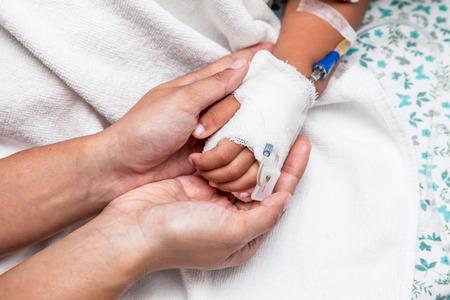 niños enfermos: madre sosteniendo la mano del niño que tiene solución intravenosa en el hospital