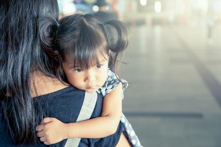 Mère et enfant, mignonne petite fille de repos sur l'épaule de sa mère dans la gare, effet de filtre vintage, mise au point sélective Banque d'images