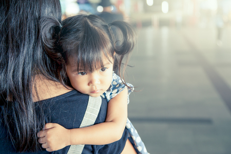 sad cute baby: Mother and child,cute little girl resting on her mothers shoulder in the train station, vintage filter effect,selective focus Stock Photo