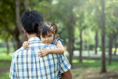 Father and child,happy little girl resting on her fathers shoulder in the park, vintage filter effect
