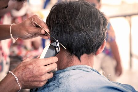 hair clippers: Old man having a haircut with a hair clippers in barber shop in vintage color filter Stock Photo