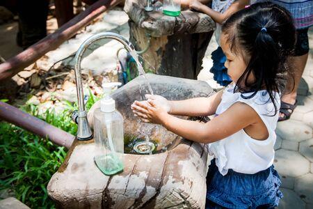lavamanos: Niña del niño que se lava la mano en el parque