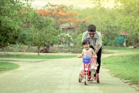 niño empujando: Niña del niño que se divierte a montar en triciclo con la familia, el padre está empujando triciclo, tono de color verde Foto de archivo