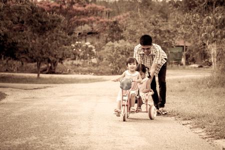 ni�o empujando: Ni�a del ni�o que se divierte a montar en triciclo con la familia, el padre est� empujando triciclo, filtro de color de la vendimia Foto de archivo