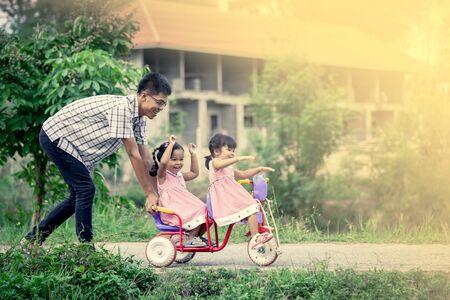 niño empujando: Niña del niño que se divierte a montar en triciclo con la familia, el padre está empujando triciclo, el tono del color de la vendimia