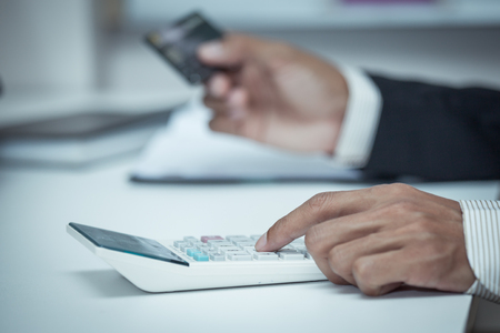 creditcard: Businessman using a calculator to calculate his payment on creditcard in vintage color filter
