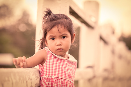 portrait of upset child in the farm in vintage color tone