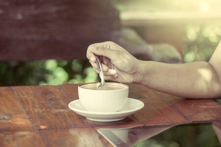 stirred: Woman hand stirred coffee in the cup in the coffee shop in vintage color filter Stock Photo