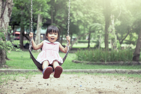 Child asian girl having fun to play swing in playground in vintage color tone