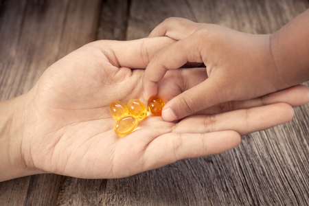 child picks Cod liver oil omega 3 gel capsules on her mother hand in vintage color tone