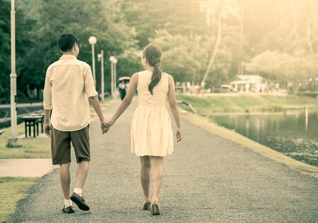 prewedding: Young couple in love holding hand and walking together in the street in vintage color tone