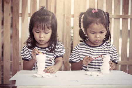 Child painting, two little girls having fun to paint on stucco doll together in vintage color tone
