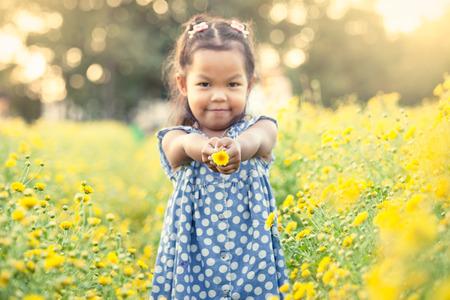 girl holding flower: Child asian little girl holding flower in her hand in the garden in vintage color tone