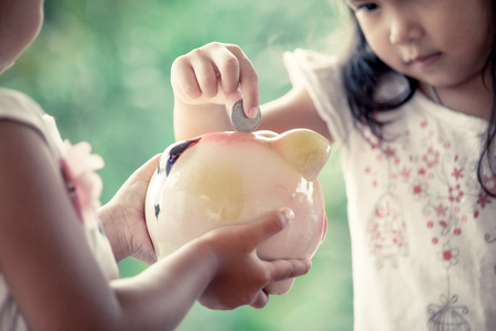 Child asian little girl putting coin into Piggy Bank in vintage color tone