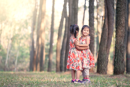 Two asian little girls having fun to play together in pine tree park in vintage color filter Stock Photo