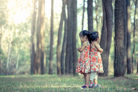two asian little girls hug their chest and turn back to each other and feel sad in vintage color tone