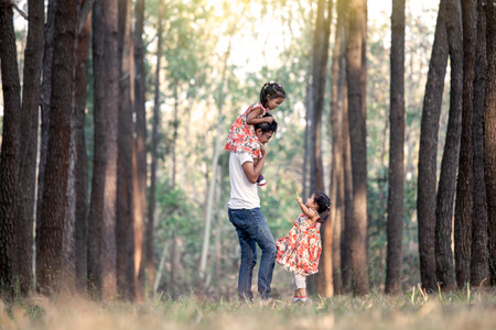 Father and daughter having fun and playing in the park and child sits on the shoulders of her father in vintage color tone Stock Photo