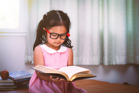 Child asian little girl put on eyeglasses reading a book in vintage color tone