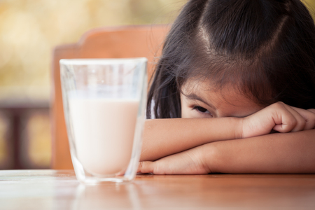 hate: Asian little girl dont need to drink milk with a glass of milk in vintage color tone